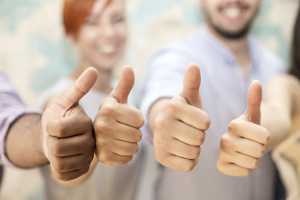 Young business people with thumbs raised up